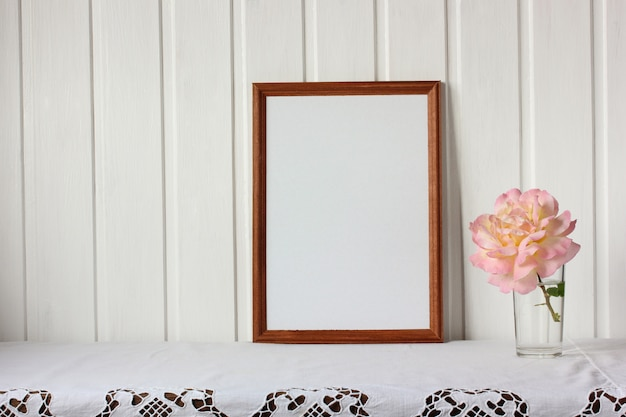 Empty rectangular frame and a rose flower. mockup, scene creator.