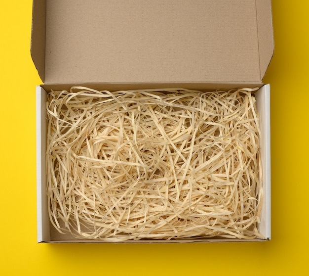 Empty rectangular open corrugated paper box with sawdust inside. packaging, containers for transportation on a yellow background