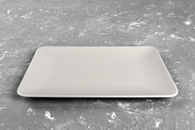 Empty rectangular plate on gray table