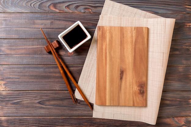 Пустая прямоугольная деревянная тарелка для суши с соусом и палочками для еды на деревянном столе