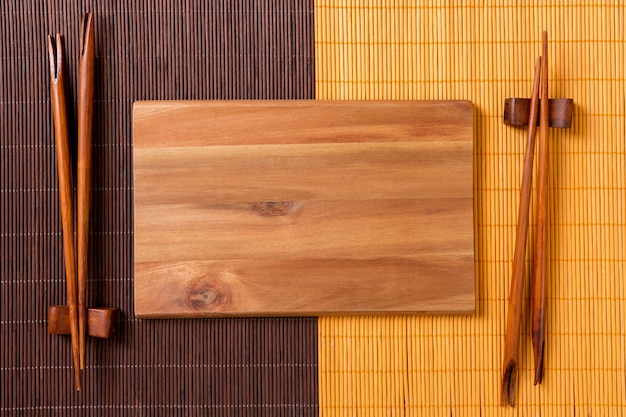 Empty rectangular wooden plate with chopsticks for sushi and soy sauce on wood surface