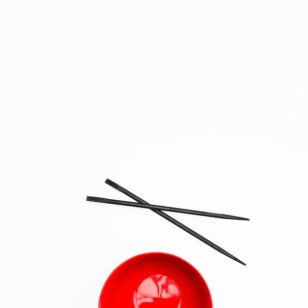 Svuoti la ciotola rossa e la bacchette isolate su fondo bianco