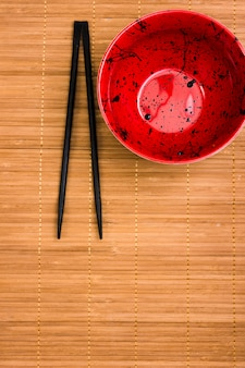 Empty red bowl with black chopsticks over brown placemat