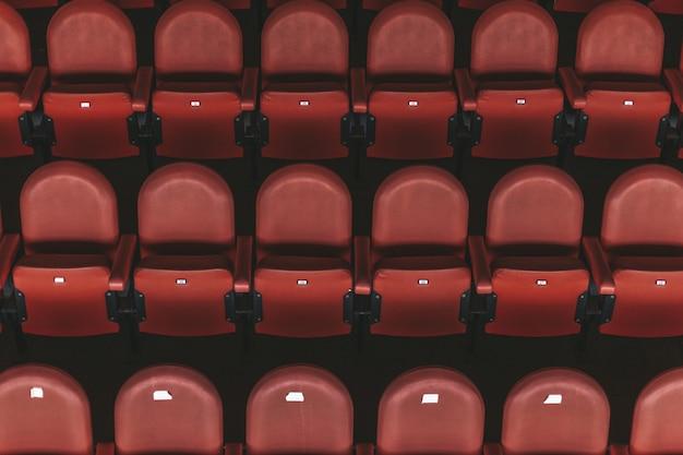 屋外アリーナの空の赤い椅子