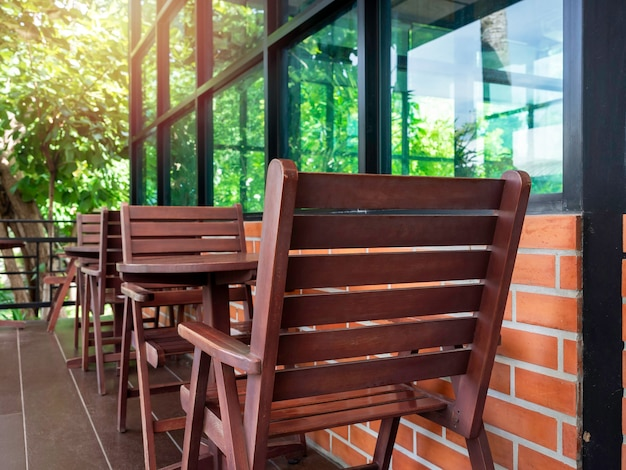 Empty red cozy wooden chairs and round wood coffee table near the glass window and brick wall with green garden in the cafe, summertime.