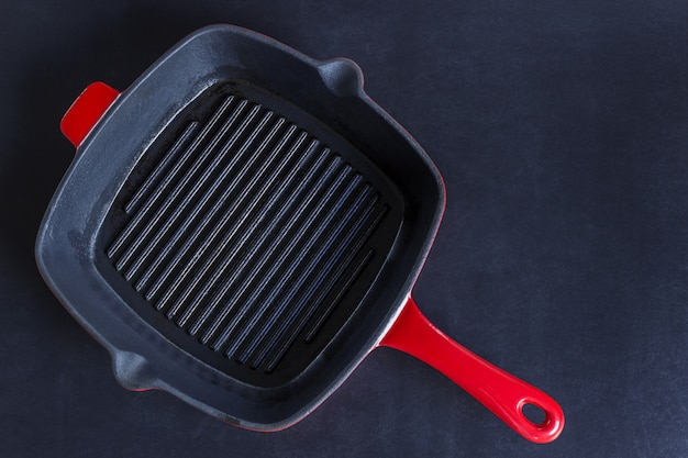 Empty red grill pan on black background.