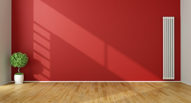 Empty red living room with radiator on red wall