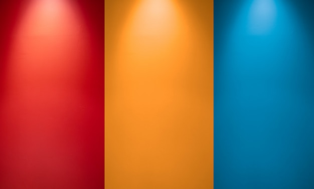 Empty red, orange or yellow and blue wall with spotlights