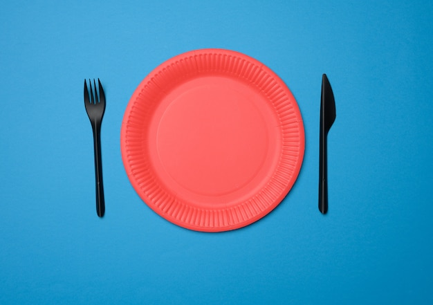 Empty red paper disposable plates on a blue background, top view