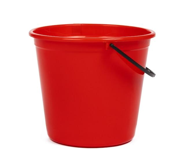 白い背景の上の空の赤いプラスチック製の家庭用バケツ