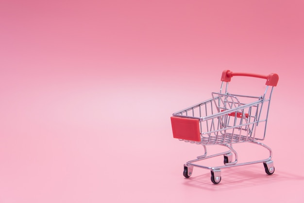 Empty red shopping cart on pink