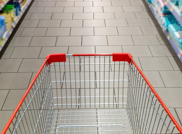 Empty red shopping cart in supermarket aisle. blurred background of aisle