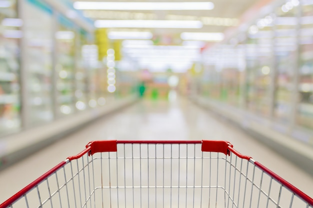 Empty red shopping cart view with milk and yogurt product shelves aisle in supermarket