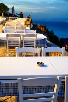 Empty restaurants with terrace in the street in afytos, greece
