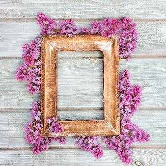 素朴なスタイルで着用した木製のホワイトボードのテーブルにライラックの花の春の枝を持つ空のレトロな木製フレーム。フリースペース