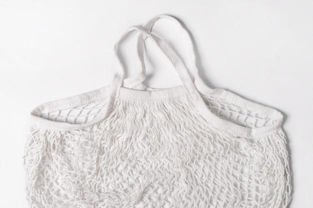 白い背景の空の再利用可能な綿ショッピング文字列バッグ。環境にやさしいネットバッグまたは買い物客。プラスチックの廃棄、廃棄物ゼロ、リサイクルおよび再利用のコンセプト。