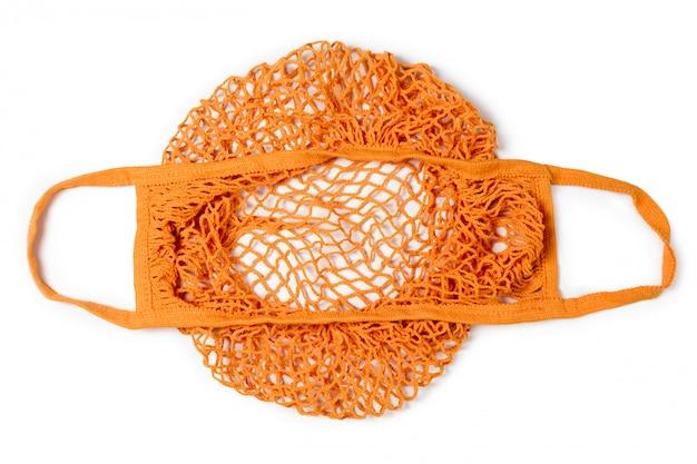 白い背景の空の再利用可能なオレンジコットンショッピング文字列バッグ。環境にやさしいネットバッグまたは買い物客。プラスチックの廃棄、廃棄物ゼロ、リサイクルおよび再利用のコンセプト。