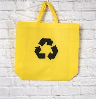 Пустой многоразовый желтый мешок из вискозы на белом, концепция сокращения пластиковых отходов