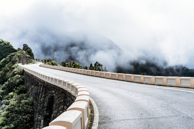 Empty road high in the mountains with cloudy foggy sky.
