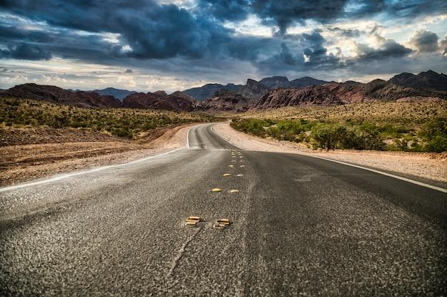 Пустая дорога в красных скалах, штат невада.