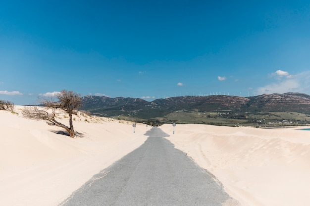 Empty road in sands against mountains