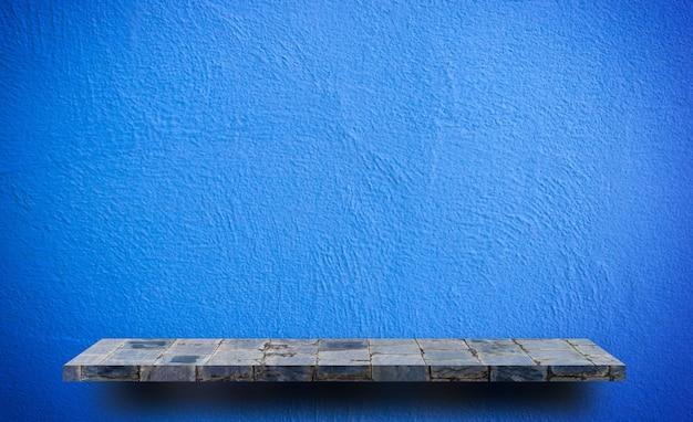 Empty rock stone shelf on blue wall background