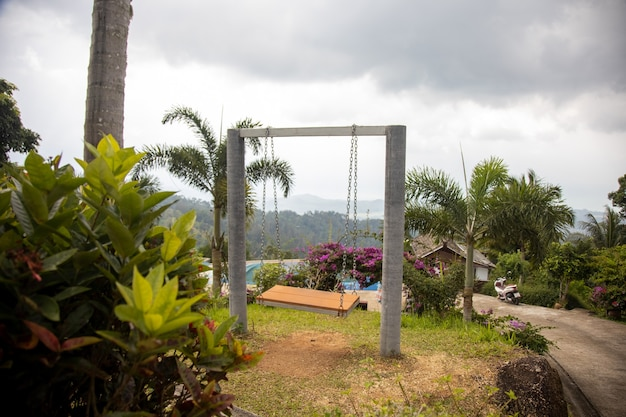 Empty romantic swing in a tropical paradise garden on a mountainside