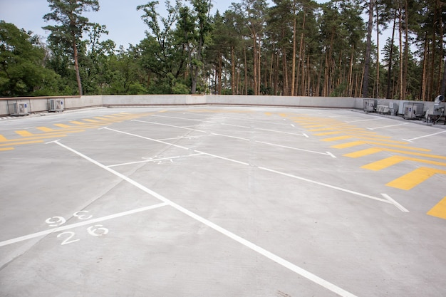 Empty rooftop parking. directional traffic arrows and parking spots are marked with white and yellow paint on the asphalt. parking space without cars with city skyline and park with trees.