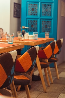 Empty room interior in blue and orange colors, served table and chairs