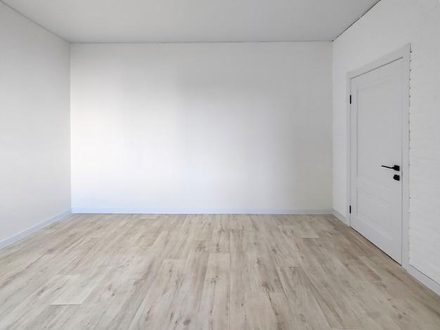 빈 방 내부 - 문과 나무 바닥이 있는 흰색 벽