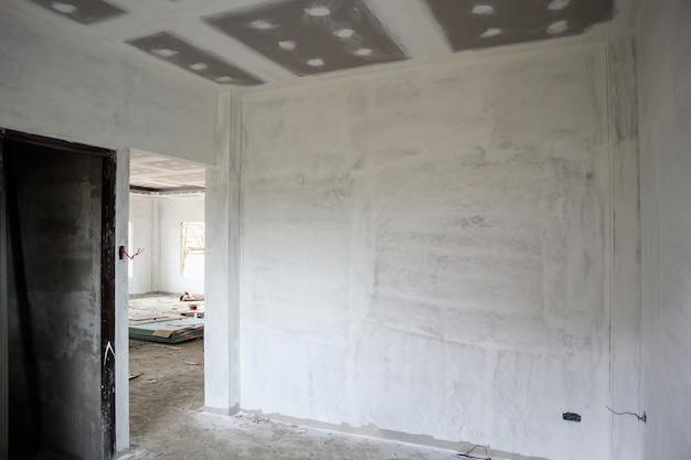 家の建設現場での石膏ボードの天井と空の部屋のインテリア