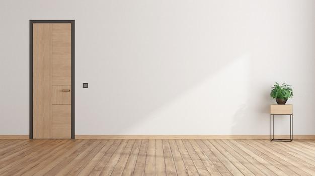 閉じたドアの白い壁とサイドテーブルに観葉植物のある空の部屋
