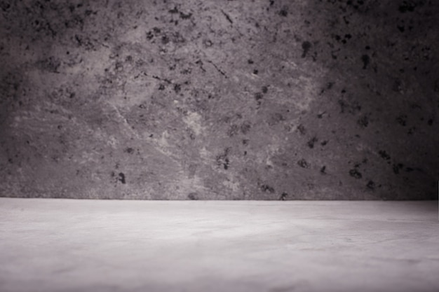 Пустая комната с бетонной стеной, серой предпосылкой.