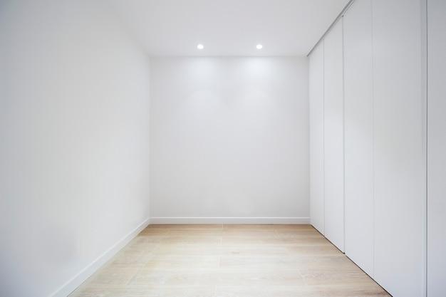 문 옷장과 흰색 벽이 있는 빈 방