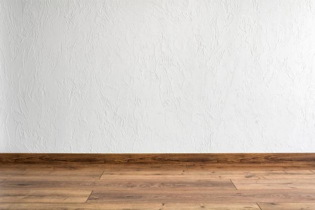 흰색 벽과 쪽모이 세공을 한 빈 방입니다. 최소한의 인테리어 디자인.