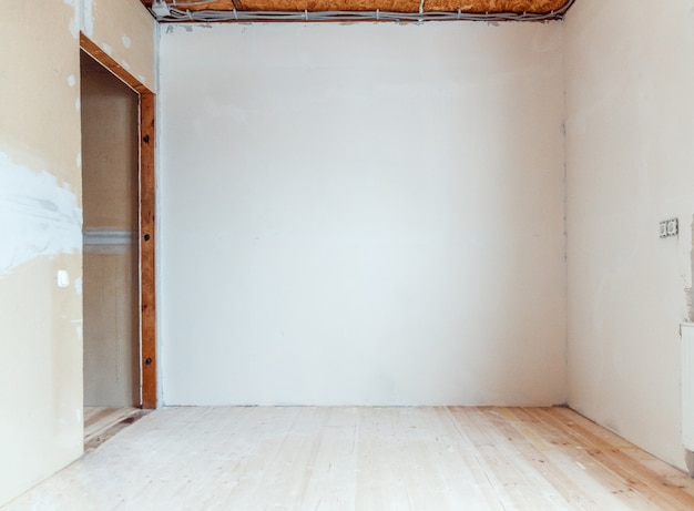 Empty room with wooden floor and newly painted white wall in background. room renovation concept.