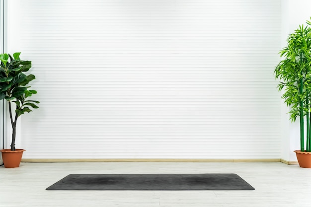 Empty room with yoga mat on floor with white wall