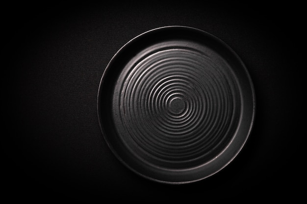 Empty round black ceramic plate with pattern of circles