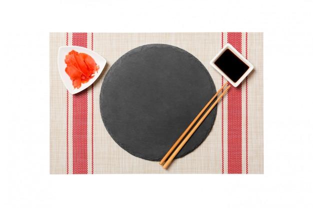 Пустая круглая черная тарелка с палочками для еды и соевым соусом, имбирь на сушином коврике