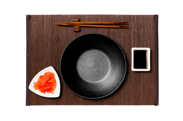 Empty round black plate with chopsticks for sushi, ginger and soy sauce on dark bamboo mat