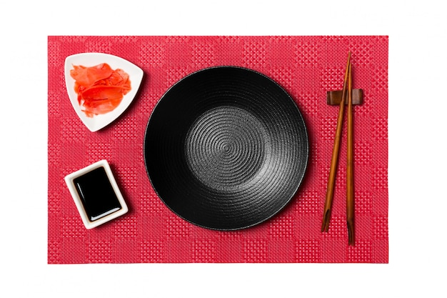 Empty round black plate with chopsticks for sushi and soy sauce, ginger on red mat sushi