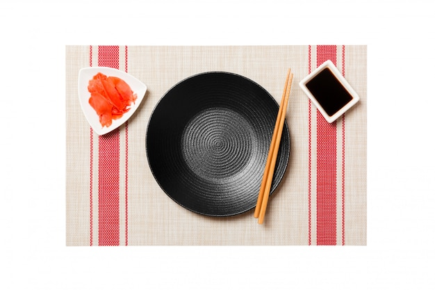 Empty round black plate with chopsticks for sushi