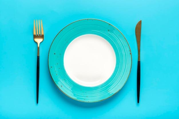파란색 테이블에 빈 둥근 파란색 접시 포크 나이프 상위 뷰 아침 점심 또는 저녁 식사를 위한 평평한 접시
