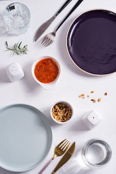 Empty round blue and purple plates with cutlery , roasted peanuts and tomato sauce. top view with copy space for you design.