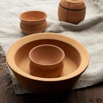 Пустая круглая коричневая тарелка стоит на серой льняной салфетке