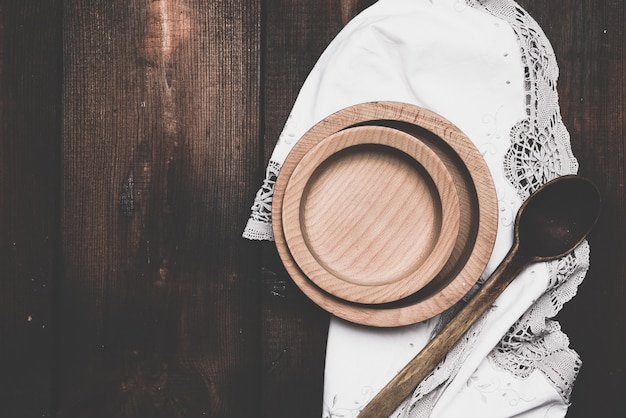 Empty round brown plate standing on a white napkin, wooden background from old boards
