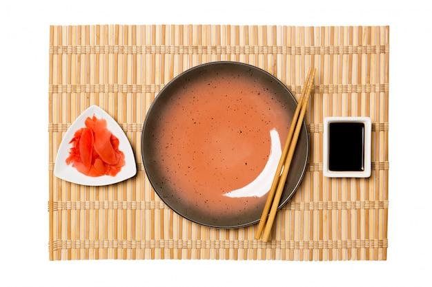 Пустая круглая коричневая тарелка с палочками для суши и соевым соусом, имбирь на желтой бамбуковой циновке. вид сверху с copyspace