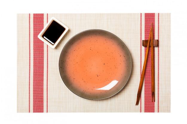 Пустая круглая коричневая тарелка с палочками для суши и соевым соусом