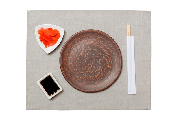 Empty round brown plate with chopsticks for sushi, ginger and soy sauce on grey napkin background. top view with copy space for you design.