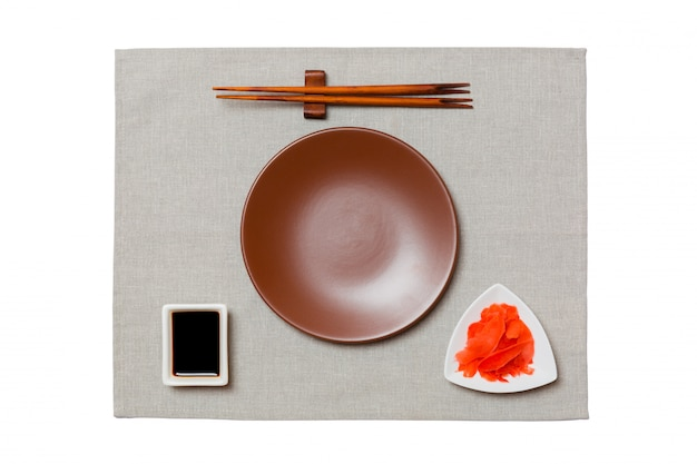 Empty round brown plate with chopsticks for sushi, ginger and soy sauce on grey napkin . top view with copyspace